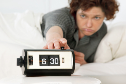 Woman hitting snooze alarm